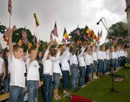 Local school children sing national anthems