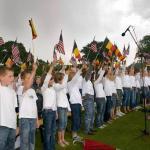 Local school children sing national anthems